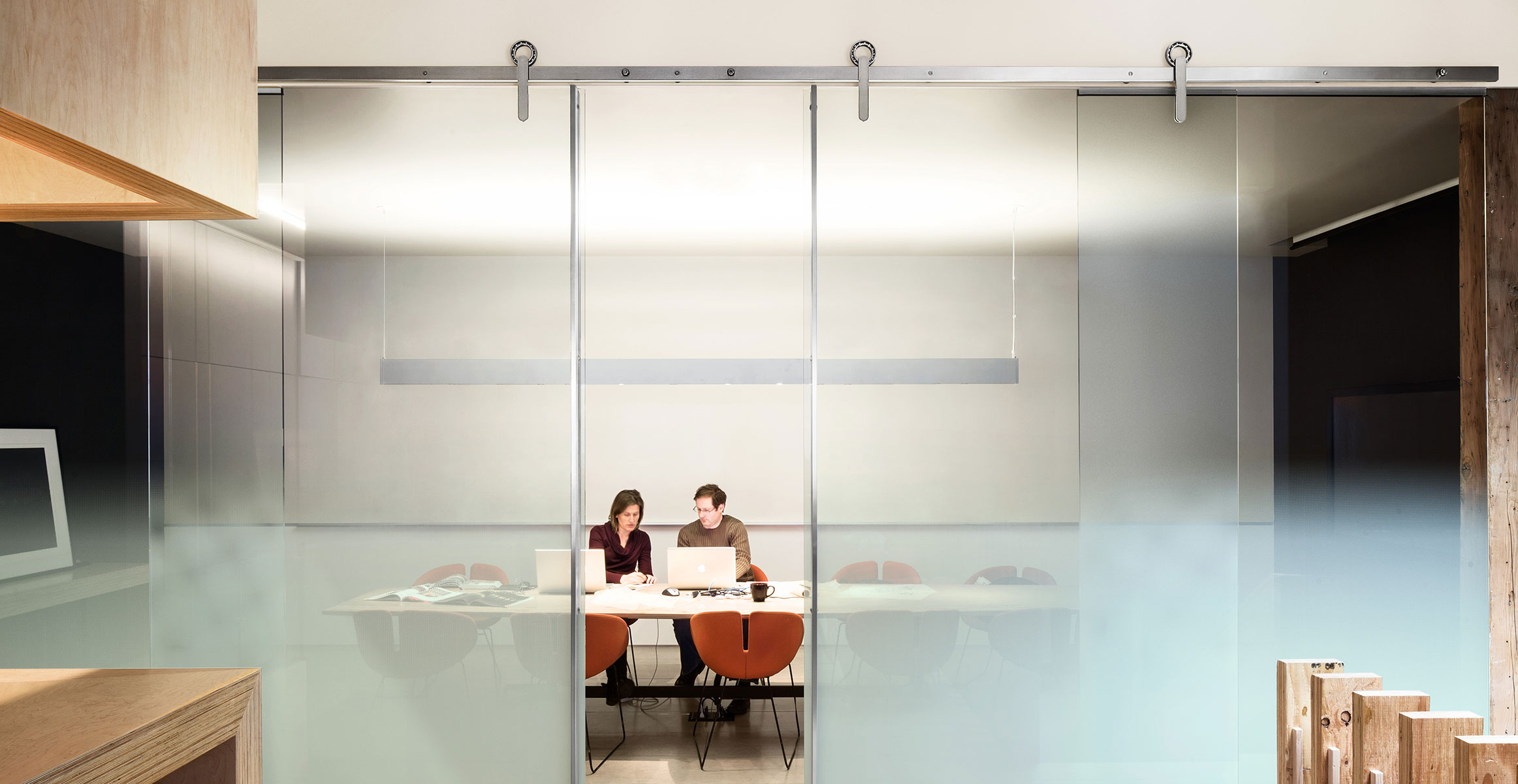 Glass conference room sliding doors with vertical stainless steel pulls