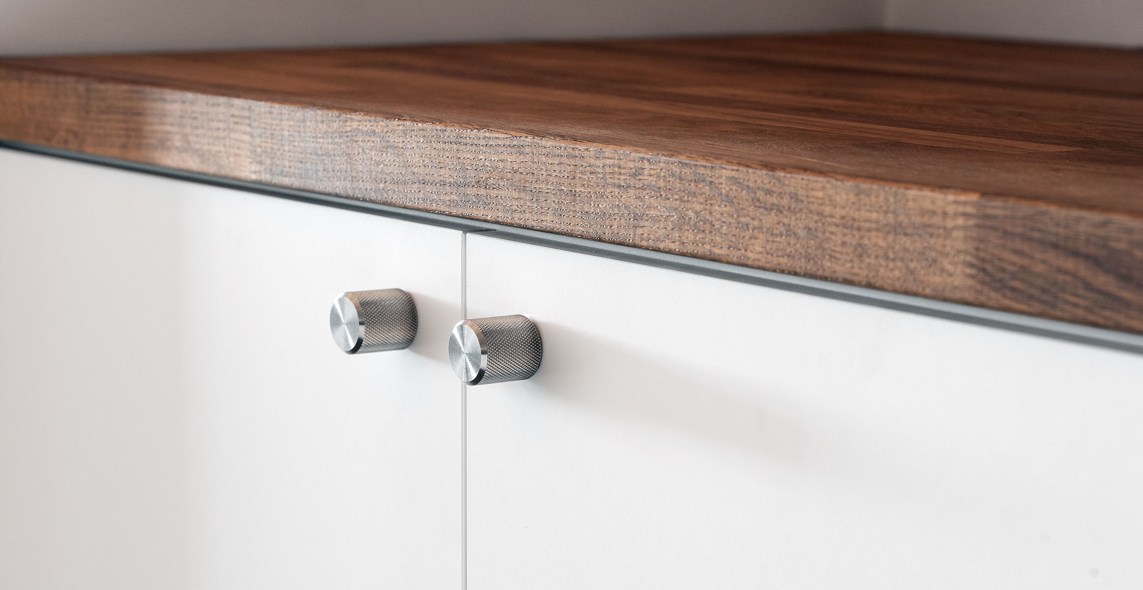 Kitchen cabinet featuring the Kor Cabinet Knob in Stainless Steel finish