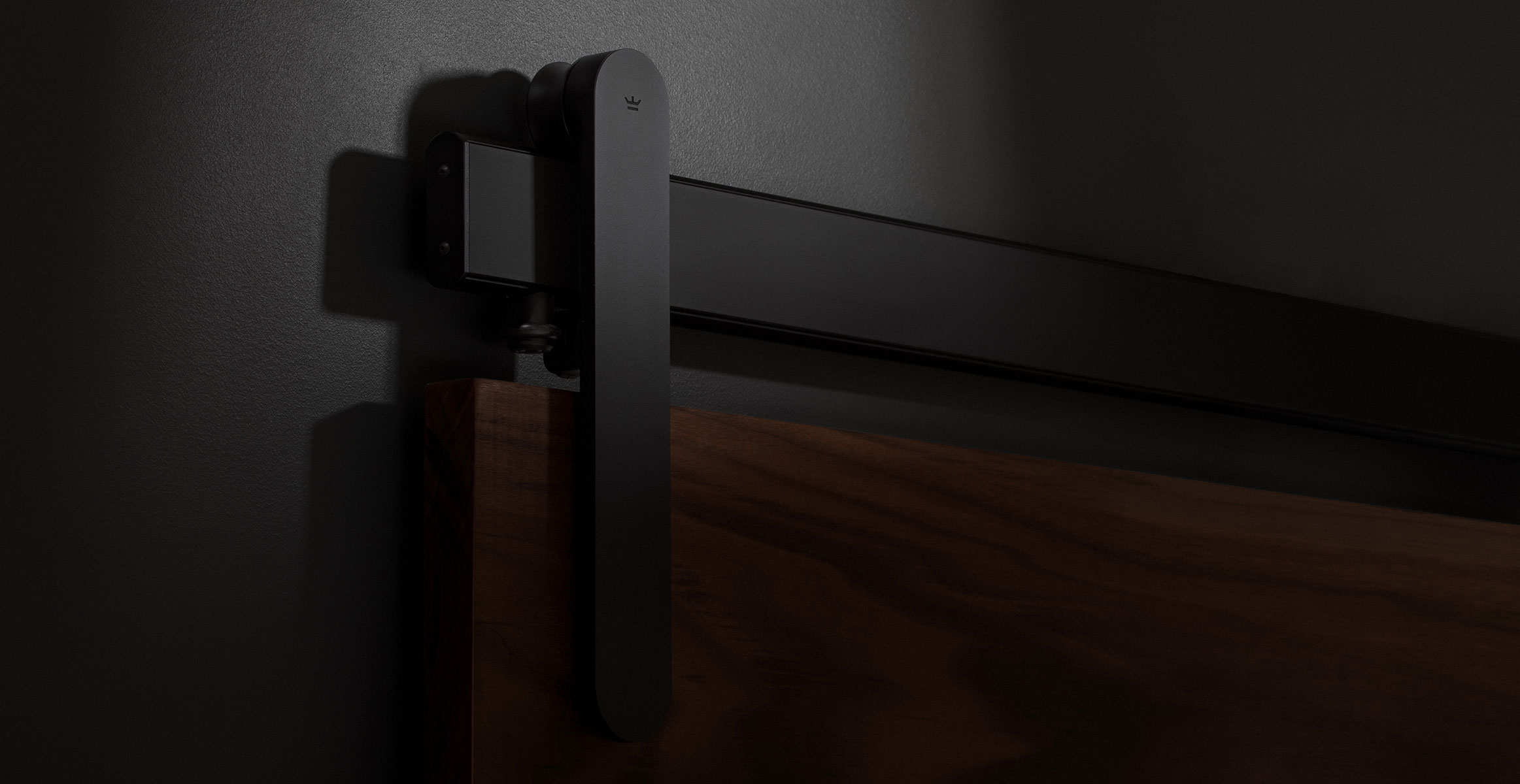 Loki sliding door hardware in Black Satin finish installed on dark walnut door panel
