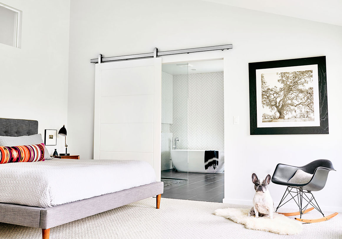 Krownlab modern sliding door hardware in brushed stainless finish with white door over bathroom entry