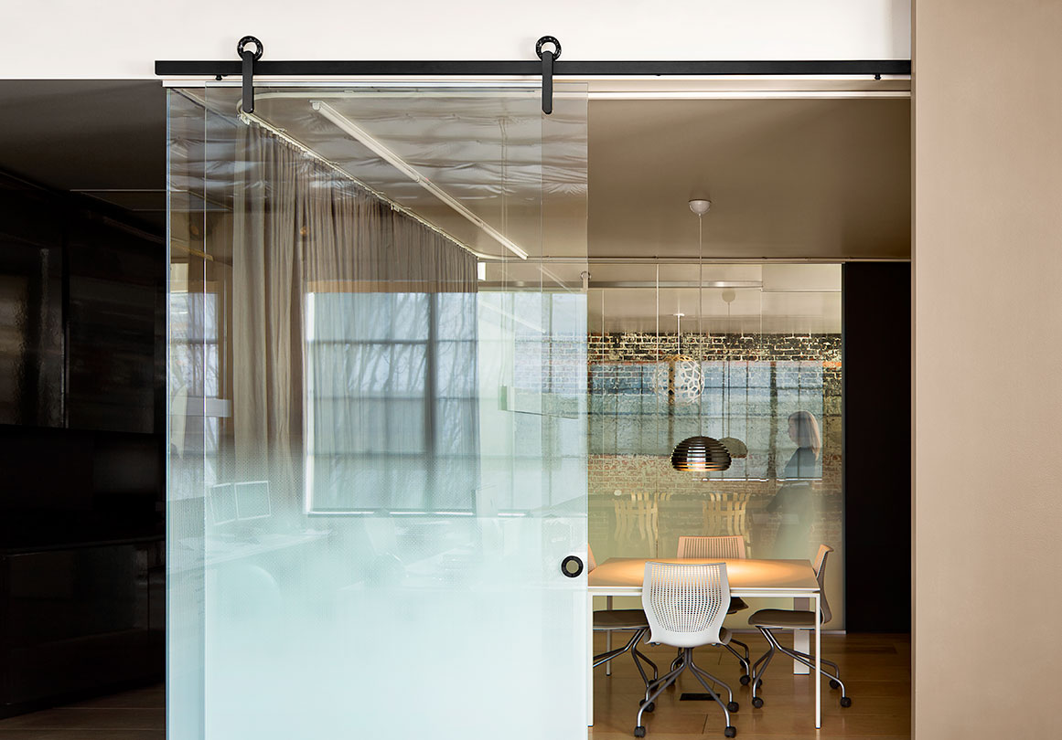 The Baldur sliding door hardware system in Skylab's Black Box Building, Portland, OR. Shown in Glass Mount with Black Stainless finish.