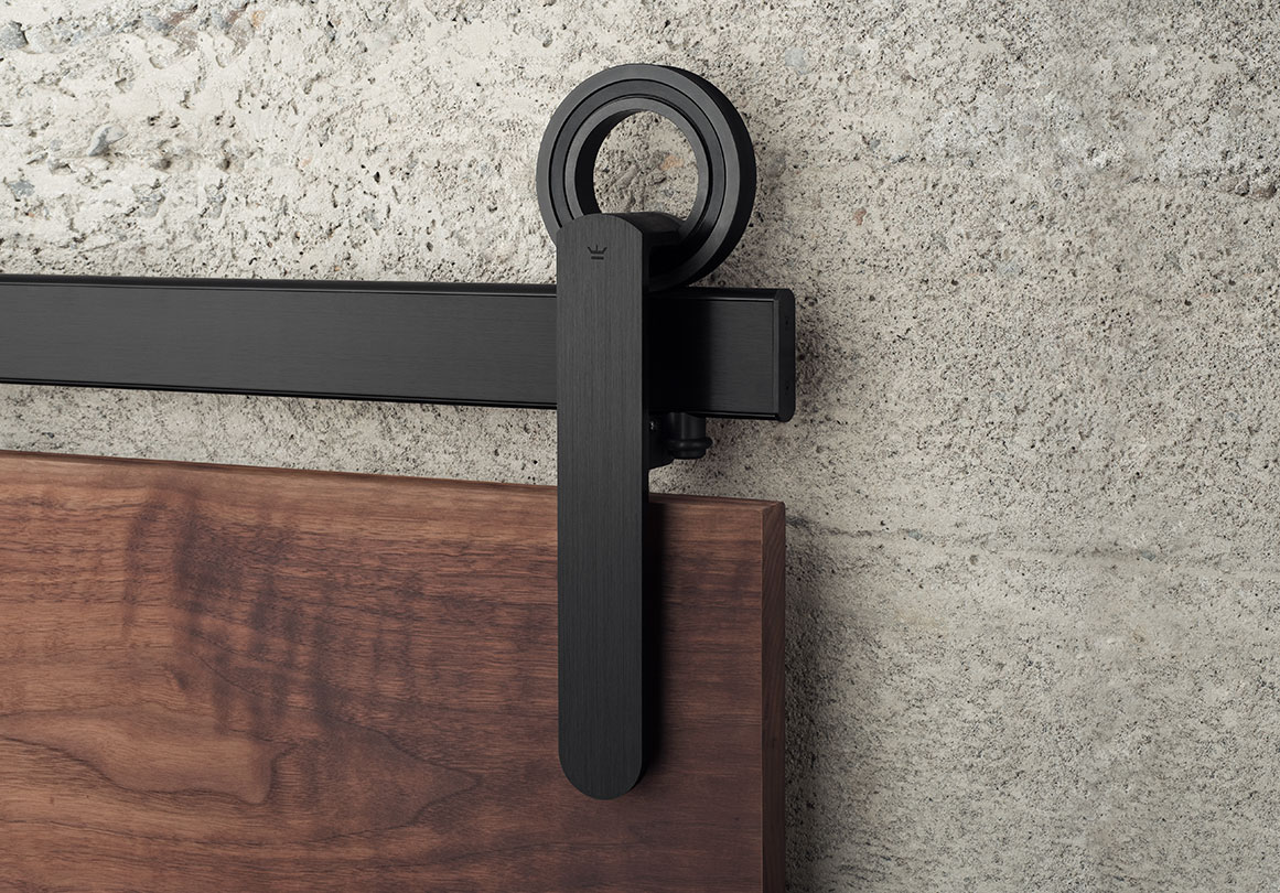 Baldur sliding door hardware in Black Stainless finish installed with a walnut panel.