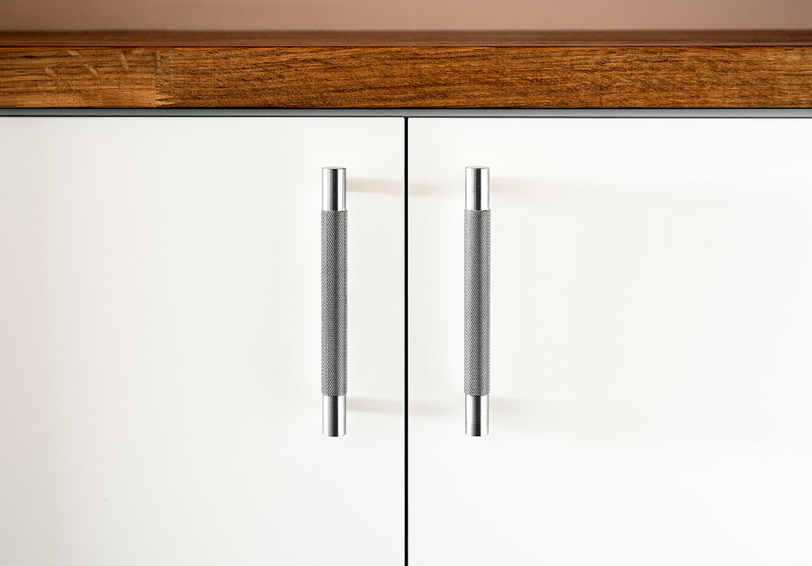 Kor Cabinet Pull in Stainless Steel with knurled texture installed on a white kitchen cabinet.