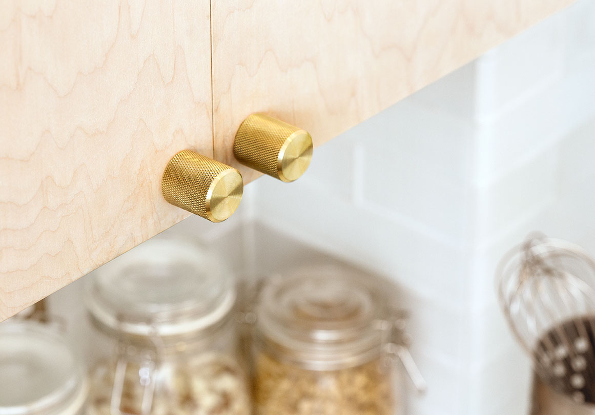 Kor Cabinet Knob in Brass finish  installed on a kitchen cabinet.