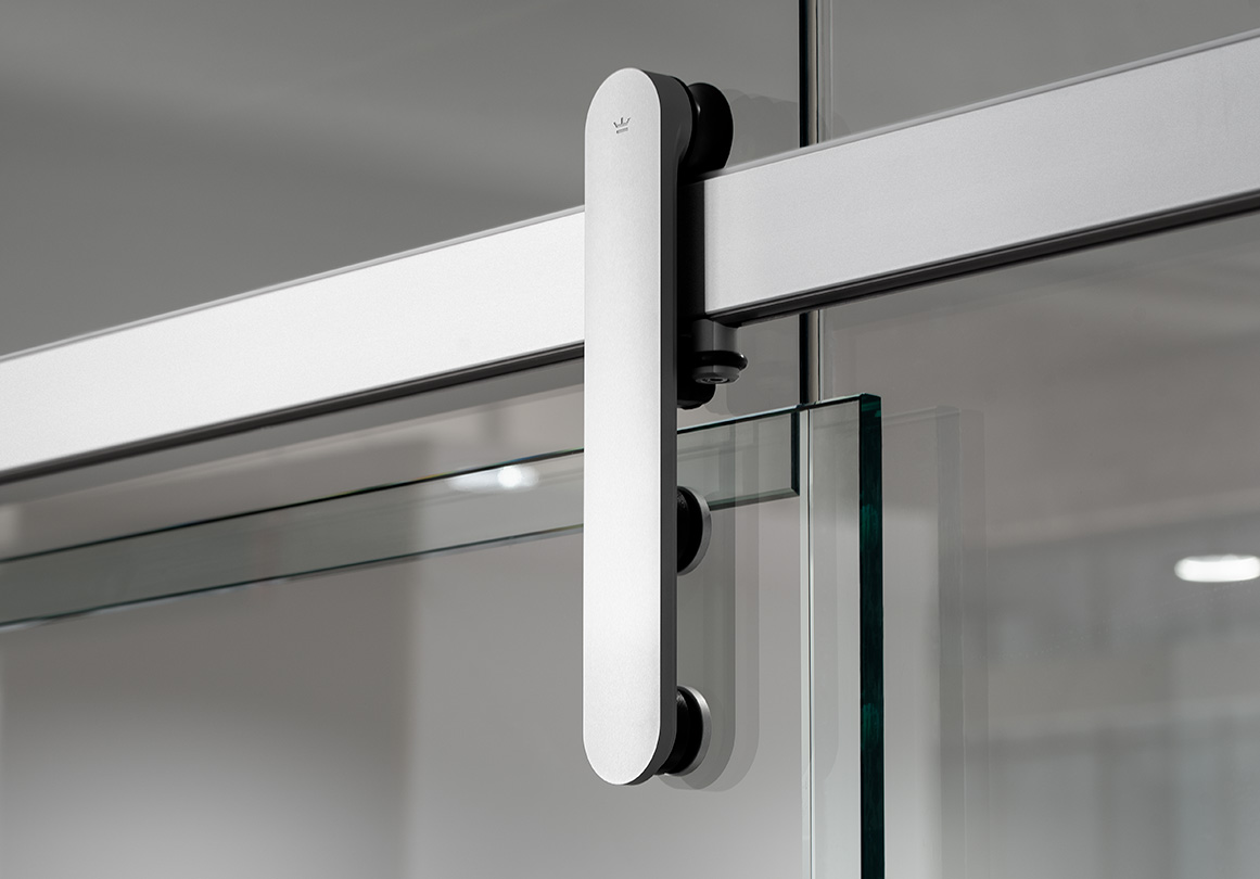 Loki sliding door hardware installed on glass office wall.