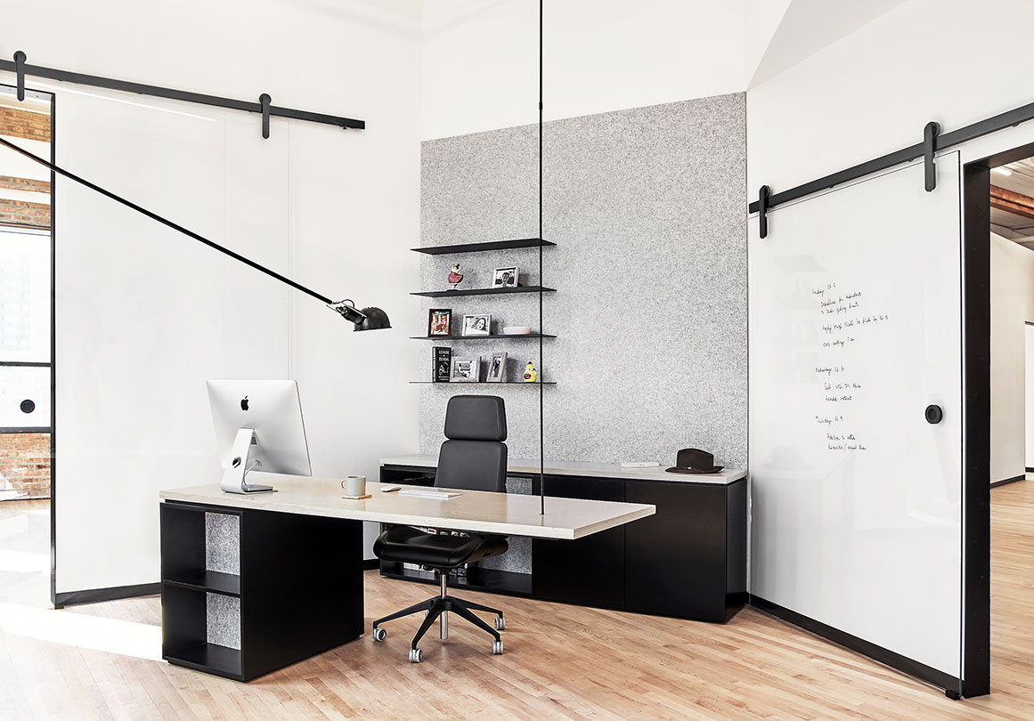 Oden sliding barn door hardware in Black Stainless installed in a modern office.