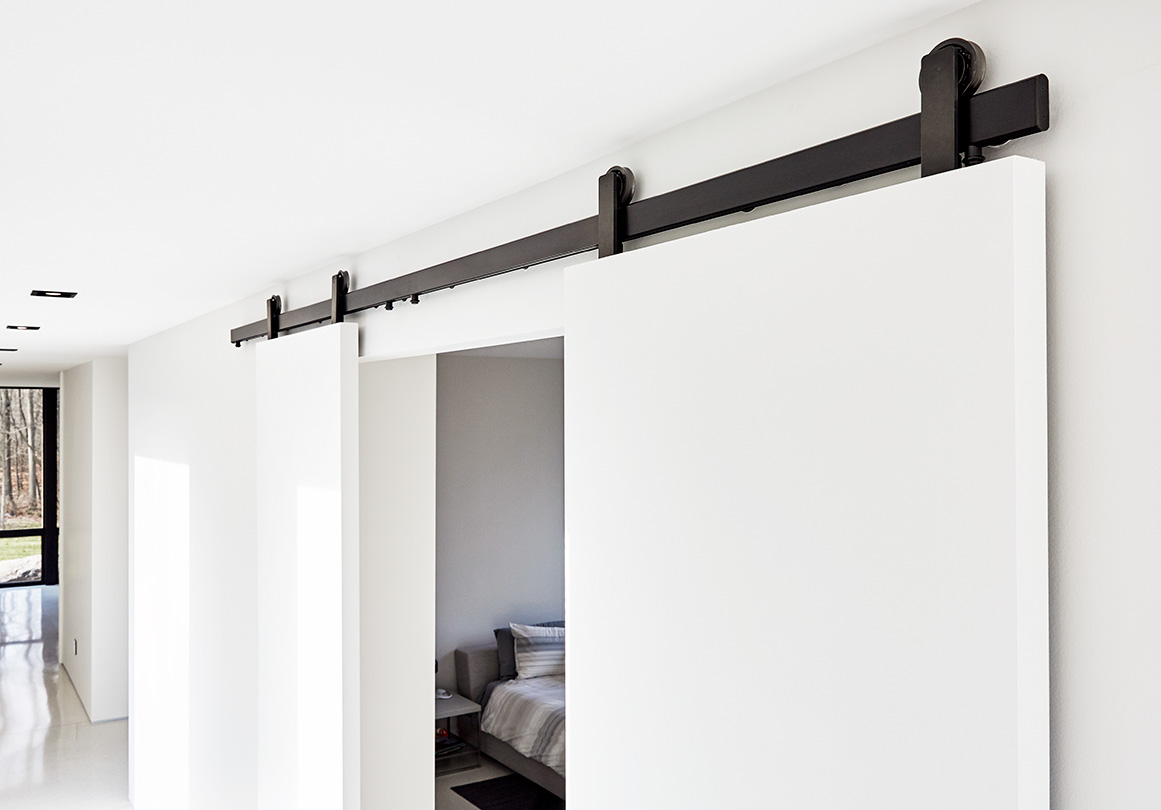 Oden sliding barn door in Black Stainless installed on white door in a private residence.
