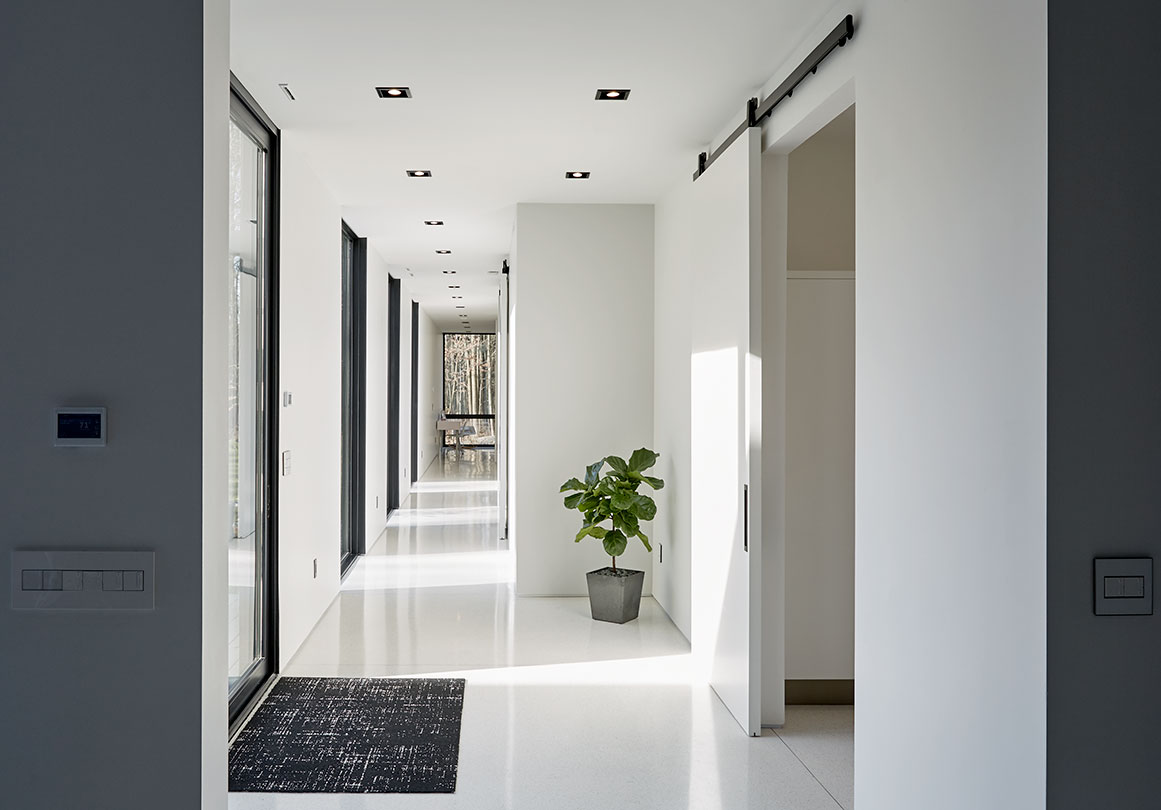 Black sliding door hardware makes a statement in a modern white interior.
